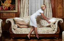 Domestica attraente che fa un sofà in albergo di lusso Fotografia Stock Libera da Diritti