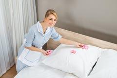 Domestica che decora camera da letto con i petali Fotografie Stock Libere da Diritti