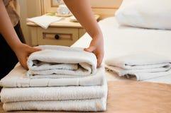 Domestica che dispone gli asciugamani lavati freschi su un letto Immagine Stock