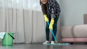 Domestica che lava con attenzione pavimento di camera di albergo prima dell'arrivo degli ospiti, pulente fotografia stock libera da diritti