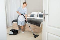 Domestica con l'aspirapolvere nella camera di albergo Fotografia Stock