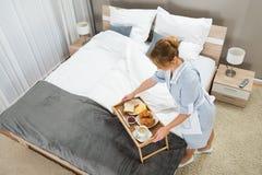 Domestica con la prima colazione che tiene sulla tavola del vassoio Immagini Stock Libere da Diritti