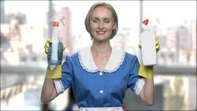 Domestica della donna che tiene due bottiglie del detersivo stock footage