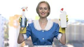 Domestica felice della donna che tiene due bottiglie del detersivo archivi video