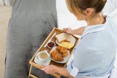 Domestica femminile con il vassoio della prima colazione Fotografie Stock Libere da Diritti