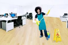 Domestica maschio che gioca con la scopa nell'ufficio immagine stock