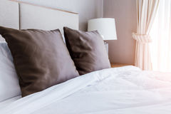 Domestica-su del letto con i cuscini marroni puliti Immagini Stock Libere da Diritti