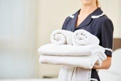 Domestique avec les serviettes fraîches pendant le ménage images stock