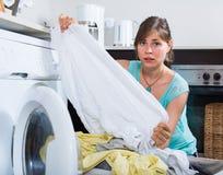 Domestique bouleversée regardant des vêtements Images libres de droits