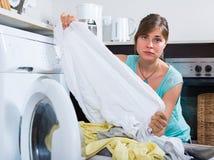 Domestique bouleversée regardant des vêtements Photos stock