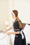 Domestique dans le lit de fabrication uniforme d'hôtel photo stock