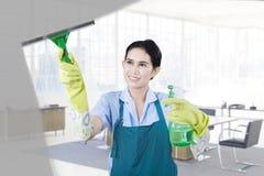 Domestique féminine nettoyant la fenêtre images libres de droits