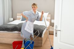 Domestique souffrant du mal de dos tout en nettoyant la chambre d'hôtel Images stock