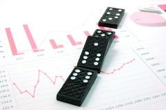 Dominó arriscado sobre uma carta de negócio financeira Imagem de Stock