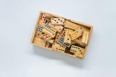 Dominós de madera en caja de madera en el fondo blanco con el foco selectivo Fotografía de archivo libre de regalías