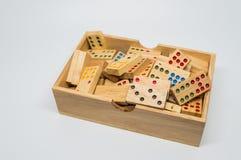 Dominós de madera en caja de madera en el fondo blanco con el foco selectivo Imagen de archivo libre de regalías