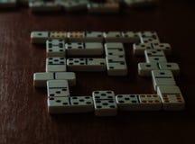 Dominós do jogo em um fundo de madeira Um jogo para quatro povos fotografia de stock