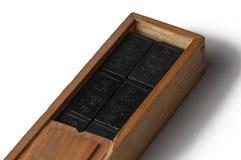 Domin?s negros en una caja de madera aislada en un fondo blanco Copie el espacio fotografía de archivo