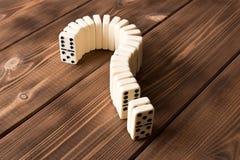 Domina znak zapytania na drewnianym stole Domino zasada zdjęcia royalty free