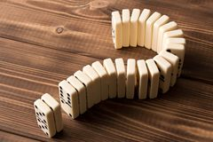 Domina znak zapytania na drewnianym stole Domino zasada fotografia royalty free