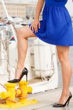 Dominant feminist woman wearing high heels in marina. Dominant feminist woman wearing high heels and short blue dress, standing one leg on big industrial bolt in Stock Photos