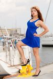 Dominant feminist woman wearing high heels in marina. Dominant feminist woman wearing high heels and short blue dress, standing one leg on big industrial bolt in Royalty Free Stock Images
