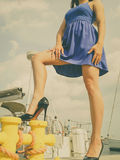 Dominant feminist woman wearing high heels in marina. Dominant feminist woman wearing high heels and short blue dress, standing one leg on big industrial bolt in Royalty Free Stock Photo