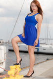 Dominant feminist woman wearing high heels in marina. Dominant feminist woman wearing high heels and short blue dress, standing one leg on big industrial bolt in Stock Image