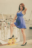 Dominant feminist woman wearing high heels in marina. Dominant feminist woman wearing high heels and short blue dress, standing one leg on big industrial bolt in Royalty Free Stock Photos