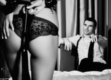 Dominant sexy womans ass in underwears with a whip standing in front of handsome guy. BDSM concept Royalty Free Stock Image