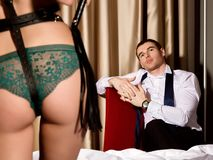 Dominant sexy womans ass in underwears with a whip standing in front of handsome guy. BDSM concept Royalty Free Stock Images