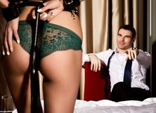 Dominant sexy womans ass in underwears with a whip standing in front of handsome guy. BDSM concept Stock Photos