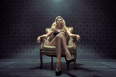 Dominating blond woman sitting on the armchair Stock Photo
