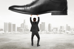 Domination concept with businessman resists pressure at city bac Stock Images