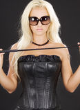 Dominatrix. In black leather corset with riding crop Stock Photography