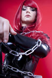 Dominatrix. Determinatively looking strict mistress in latex catsuit and cold steel chains Royalty Free Stock Photos
