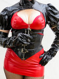 Dominatrix in PVC holding a key. Close up of dominatrix body in a red and black PVC outfit holding a key Stock Photography