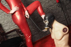 Dominatrix in red latex play with gas mask Royalty Free Stock Images