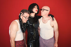 Dominatrix with Two Men. Confident dominatrix holds two insecure men around her Royalty Free Stock Image