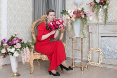 Domineering woman is posing in red dress. In studio stock photography