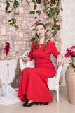 Domineering woman is posing in red dress. In studio stock photo
