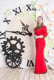Domineering woman is posing in red dress. In studio stock images