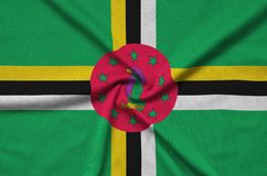 Dominica flag is depicted on a sports cloth fabric with many folds. Sport team banner. Dominica flag is depicted on a sports cloth fabric with many folds. Sport royalty free stock image