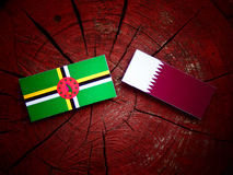 Dominica flag with Qatari flag on a tree stump isolated. Dominica flag with Qatari flag on a tree stump Royalty Free Stock Images