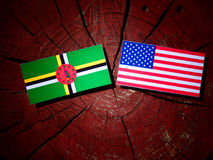 Dominica flag with USA flag on a tree stump stock photo