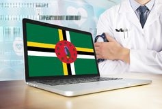 Dominica healthcare system in tech theme. Dominican flag on computer screen. Doctor standing with stethoscope in hospital. Cryptocurrency and Blockchain royalty free stock photos