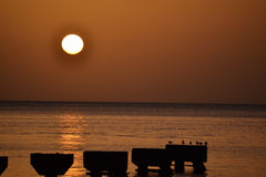 Dominica Island Sunset. With pier and shadows and silhouettes royalty free stock image