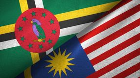 Dominica and Malaysia two flags textile cloth, fabric texture. Dominica and Malaysia flags together textile cloth, fabric texture royalty free stock photos