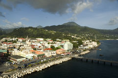 Dominica Village in Sunlight. Village on Dominica spotlighted with sunlight and clouds overhead Stock Photo