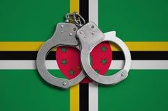 Dominica vlag en politiehandcuffs Het concept naleving van de wet in het land en bescherming tegen misdaad royalty-vrije stock afbeeldingen